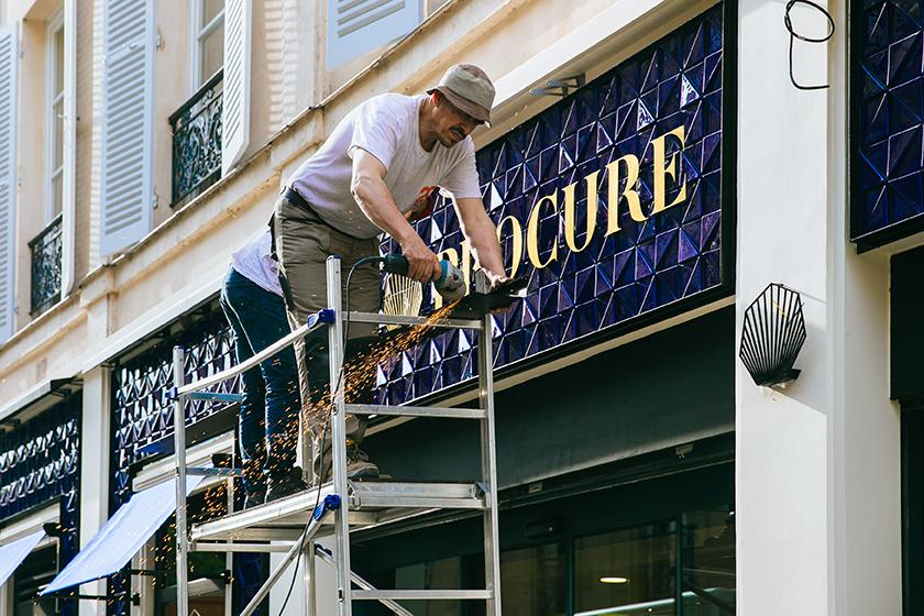 18 juin 2019 : Ouvriers qui terminent la nouvelle facade de la librairie La Procure à l'occasion de son centenaire. Paris (75), France.